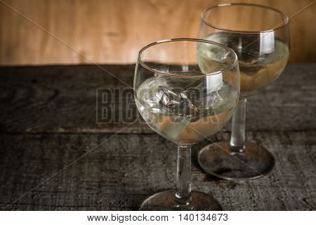 Glasses with white wine on rustic wood background, copy space