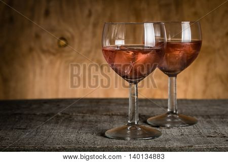 Glasses with rose wine on rustic wood background, copy space