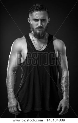 Handsome Bearded Man With Tattoo In Black T-shirt Posing On Background. Model Tests