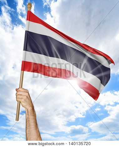 Person's hand holding the Thai national flag and waving it in the sky, 3D rendering