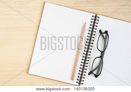 Desk above Top view of open spiral notebook with brown pencil and black eye glasses on wooden background