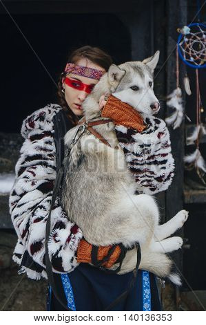 american indian girl with makeup in winter with a dog