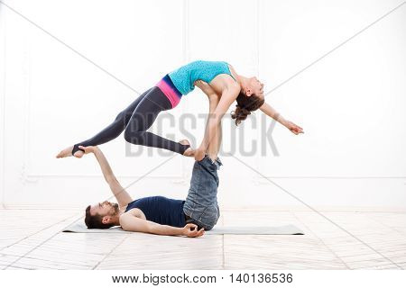Young Beautiful Man And Woman Practicing Acroyoga Doing Excercise In White Interior