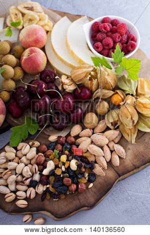 Fruit and nuts snack board including melon, cherry, almonds and pistachios