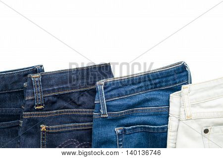 Isolated folded jeans denim trousers in different blue color from light to dark on white background