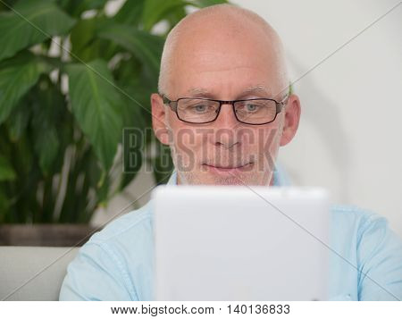 a portrait of a mature man with a tablet