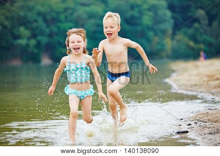 Two happy kids running through sea water in summer