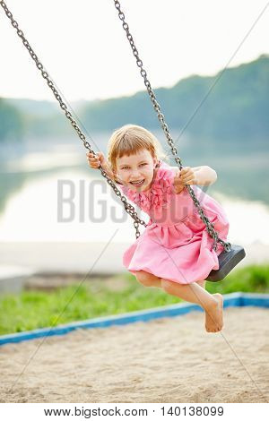 Happy girl swinging on swing in summer on a playground