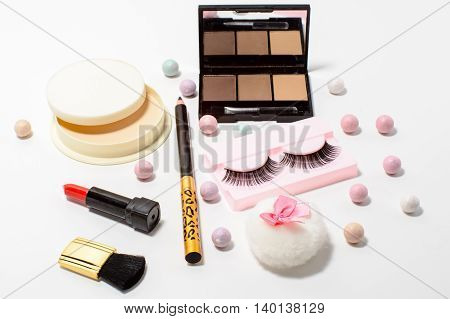 Set of decorative cosmetics false eyelashes powder lipstick eye shadow white background. Top view of essentials for modern young woman.
