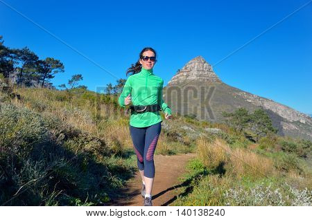 Active woman runner runs trail near Table mountain, Cape Town, South Africa. Running and fitness concept