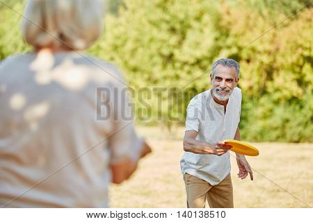 Active seniors playing with a flying disc in summer in the nature