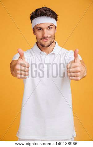 Confident attractive young man athlete showing thumbs up with both hands over yellow background