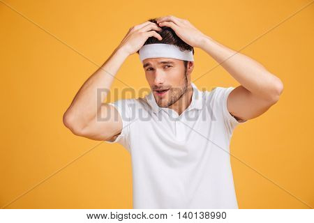 Gorgeous confident young sportsman touching his hair and posing over yellow background