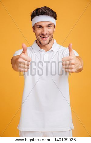 Cheerful handsome young sportsman showing thumbs up with both hands over yellow background