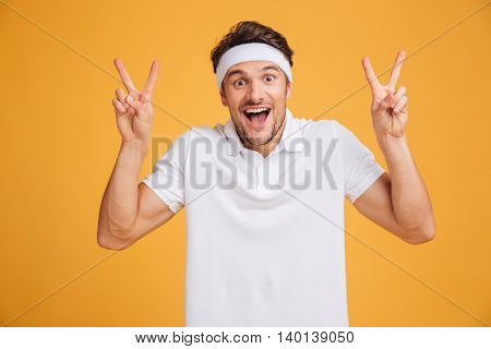 Happy excited young male athlete shouting and showing victory sign with both hands over yellow background