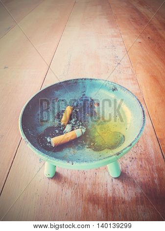 cigarette and metal ashtray on wooden table vintage filter effect