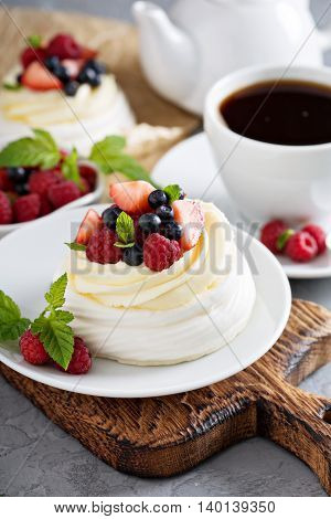 Pavlova cakes with cream and fresh summer berries