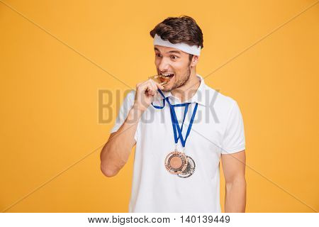 Closeup of handsome young man athlete biting his medal over yellow background