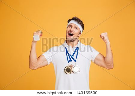 Successful cheerful young sportsman with three medals shouting and celebrating victory over yellow background