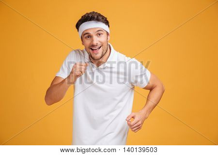 Happy young sportsman smiling and running over yellow background