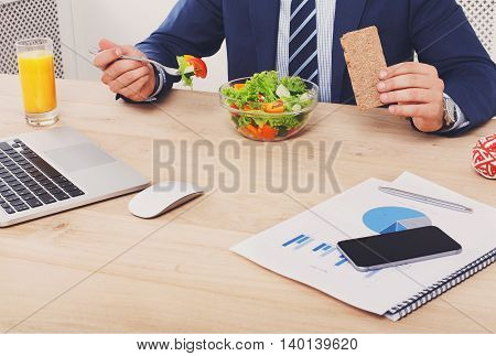 Business lunch at working place. Businessman in office. Healthy, diet food, vegetable salad with orange juice. Cell phone, laptop and papers, fitness bracelet on hand.
