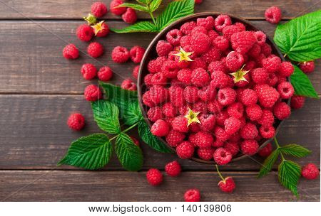 Red fresh raspberries on brown rustic wood background. Bowl with natural ripe organic berries with peduncles and green leaves on wooden table, top view with copy space