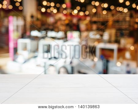 White wooden board empty table in front of blurred background. Perspective white wood over blur in shopping shoes store. Mockup for display or montage of product.