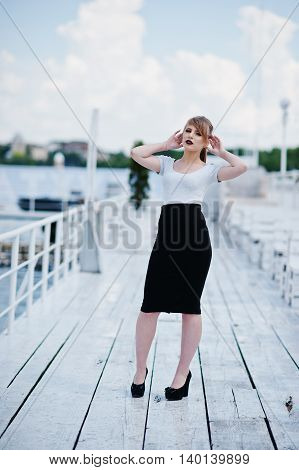 Young Blonde Girl With Black Lips On Black Skirts And White Shirt Posed On The Pier