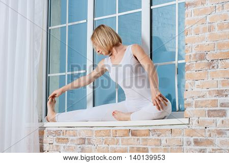 Young Beautiful Woman Practicing Yoga Doing Excercise On A Windowsill