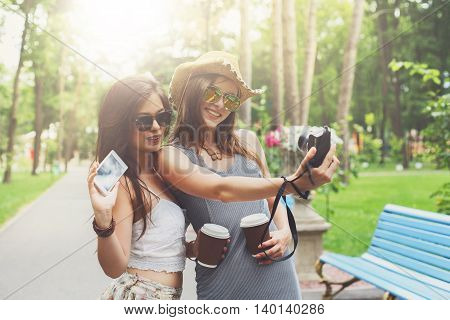 Two girls friends outdoors watching photos at digital camera. Young female tourists in boho chic fashion clothes, laighing and having fun in summer park. Travelling together, lifestyle portrait.
