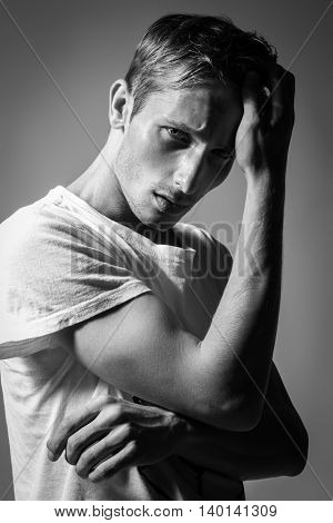 Handsome Man With Perfect Body Pulling Up T-shirt And Posing On Background. Model Tests