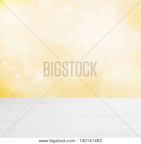 White wooden board empty table in abstract gold background with bokeh. Perspective white wood board over blurred yellow background - mockup for display of product