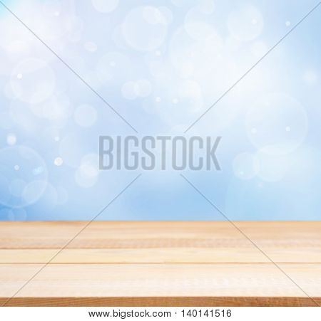 Wooden board empty table in abstract blue background with bokeh. Perspective light wood board over blurred blue background - mockup for display of product