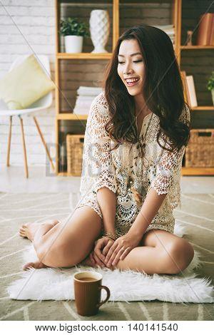 Attractive young Asian woman sitting on the floor