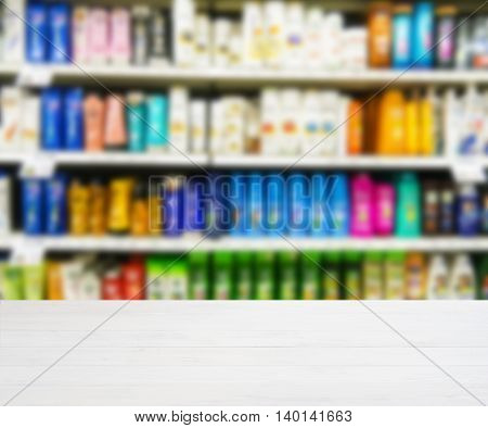 White wooden board empty table in front of blurred background. Perspective white wood board over blurred colorful supermarket products on shelvest - mockup for display of product