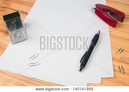 White blank paper and some office supplies on wooden table.
