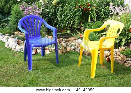 Blue and yellow plastic chairs in garden under sunlight