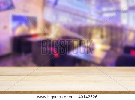 Wooden board empty table in front of blurred background. Perspective light wood over blur in cafe interior - can be used for display or montage your products. Mockup your products