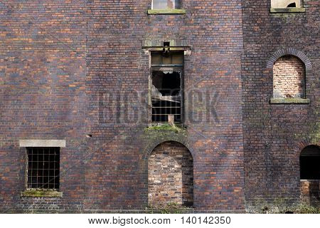 Side view of an abandoned red brick warehouse or factory building with boarded up and broken windows in Stoke-on-Trent, England
