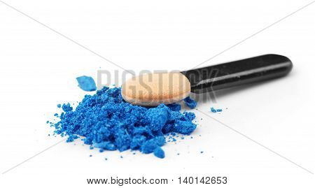Professional make-up brush on blue crushed eyeshadow