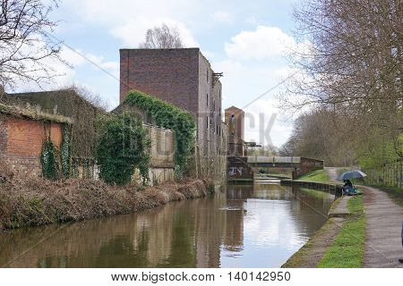 STOKE-ON-TRENT, UK - MARCH 29: A lone man fishes from a public footpath, alongside a canal running through a derelict industrial area of Stoke-on-Trent, England on March 29, 2016.