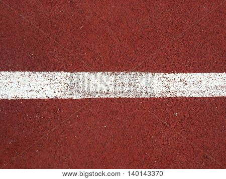 Surface perspective left to right of white line on the rubberized running track