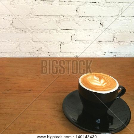Closeup a cup of latte art on the wood table with blur bokeh white brick block background