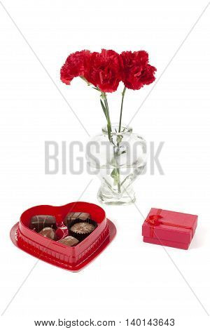 a red flower with chocolates and jewelry