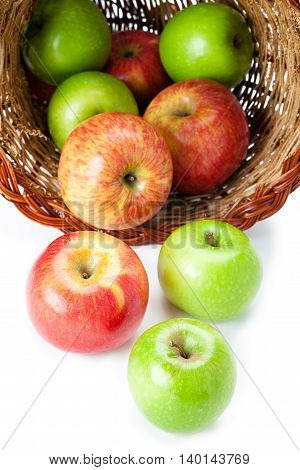 apples spilling out of basket isolated on white background