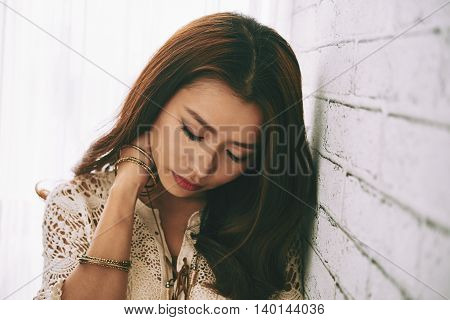 Young woman suffering from pain in her neck