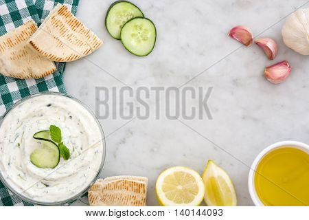 Tzatziki sauce in bowl and ingredients on white marble