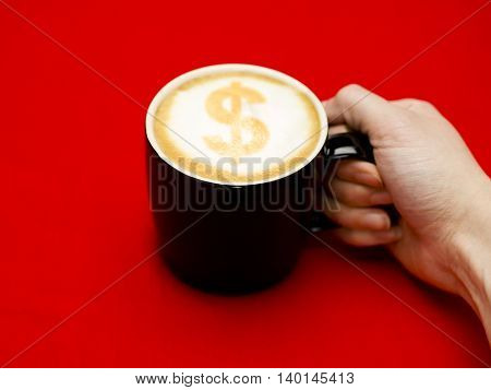 hand grabbing coffee cup with dollar sign