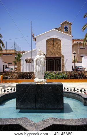 ESTEPONA, SPAIN - JULY 18, 2008 - Mother and child fountain in a town square with a church to the rear Estepona Malaga Province Andalusia Spain Western Europe, July 18, 2008.