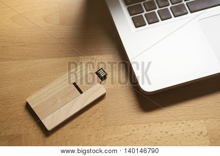 Wooden USB flash drive on a wooden table with a laptop
